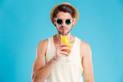 Giovane attraente in cappello ed occhiali da sole che beve succo d'arancia fotografie stock