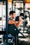 Giovane attraente che fa esercizio pesante per il bicipite sulla macchina in una palestra immagini stock