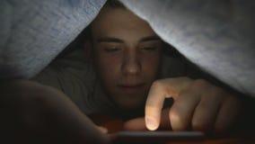 Giovane attraente che passa in rassegna media sociali su uno Smart Phone a letto stock footage