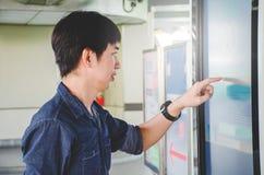 Giovane attraente che sta grande schermo digitale anteriore con i dati di mappa di base, controllo sensibile commovente maschio l immagini stock