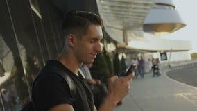 Giovane attraente in maglietta nera facendo uso del suo smartphone, legante e facente scorrere All'aeroporto o all'autostazione video d archivio