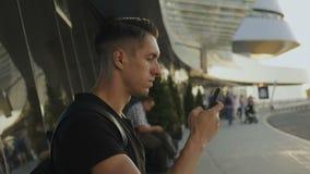Giovane attraente in maglietta nera facendo uso del suo smartphone, legante e facente scorrere All'aeroporto o all'autostazione stock footage
