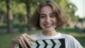 Giovane attrice seria che esamina macchina fotografica, ridente dopo il ciac che è usando video d archivio