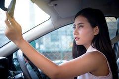 Giovane autista attraente della donna che si siede sul sedile dentro l'automobile facendo uso della h Fotografia Stock Libera da Diritti