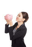 Giovane bacio asiatico della donna di affari una banca di moneta rosa Immagini Stock Libere da Diritti