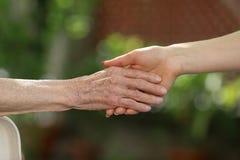 Giovane badante che tiene le mani degli anziani Mani amiche, concetto di assistenza agli'anziani fotografie stock libere da diritti