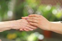 Giovane badante che tiene le mani degli anziani Mani amiche, concetto di assistenza agli'anziani immagine stock libera da diritti