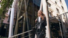 Giovane ballare biondo attraente allegro mentre scendendo scale che ascoltano la musica in cuffie all'aperto vicino a moderno video d archivio