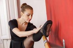 Giovane ballerina che allunga la sua gamba alla sbarra Fotografia Stock Libera da Diritti