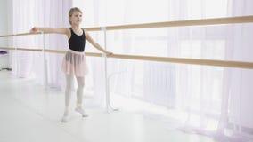 Giovane ballerina che fa gli esercizi vicino alla sbarra di balletto nello studio stock footage