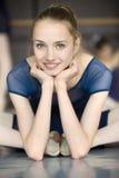 Giovane ballerina che si siede sul pavimento con il suo fronte alla macchina fotografica Immagine Stock