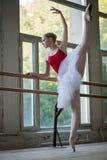 Giovane ballerina che sta su una gamba sulle vostre dita del piede nel pointe e nella d Fotografie Stock