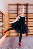 Giovane ballerina sorridente che porta tutu nero che fa esercizio nel corridoio di addestramento Immagine Stock