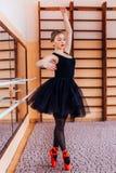 Giovane ballerina sorridente che porta tutu nero che fa esercizio nel corridoio di addestramento Immagini Stock
