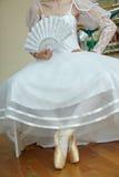 Giovane ballerina in vestito bianco che tiene un fan bianco Immagine Stock