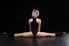 Giovane ballerino atletico della donna che allunga sul nero Fotografie Stock