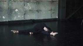 Giovane ballerino di balletto maschio che fa allungando seduta sul pavimento video d archivio