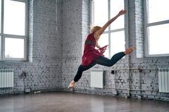 Giovane ballerino femminile che salta e che balla nella palestra Fotografia Stock Libera da Diritti