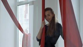 Giovane ballerino femminile del palo che sta vicino ad un tessuto aereo e che esamina macchina fotografica, sorridente Fotografia Stock