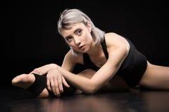 Giovane ballerino sportivo della donna che allunga sul nero Fotografia Stock