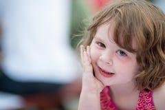 Giovane bambina che si siede e che sembra felice Immagini Stock Libere da Diritti