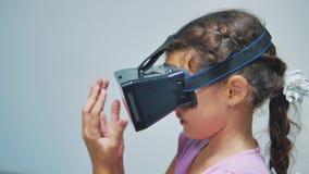 Giovane bambina felice che usando gli occhiali di protezione 3d una cuffia avricolare di realtà virtuale Donna sorpresa con il di archivi video