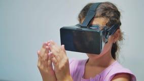 Giovane bambina felice che usando gli occhiali di protezione 3d una cuffia avricolare di realtà virtuale Donna sorpresa con il di video d archivio