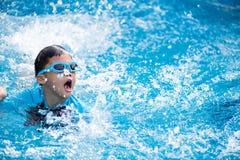 Giovane bambino asiatico felice con gli occhiali di protezione di nuotata che nuota nello stagno fotografia stock