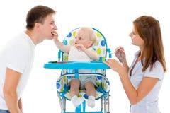 Giovane bambino dell'alimentazione dei genitori. Fotografia Stock