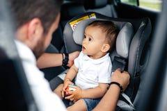 Giovane bambino della legatura del padre nel sedile del bambino dell'automobile fotografia stock