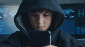 Giovane bambino incappucciato del pirata informatico facendo uso di un dispositivo dello smartphone da dirottare La meraviglia de video d archivio