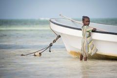 Giovane bambino locale che gioca in peschereccio al villaggio di Kiwengwa, Zanzibar immagini stock libere da diritti