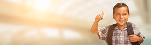 Giovane bambino maschio ispano che mostra i pollici su che indossano spirito dello zaino Fotografie Stock Libere da Diritti
