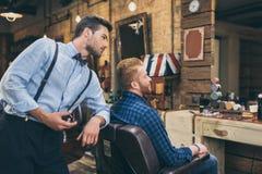 Giovane barbiere alla moda con le forbici che stanno dietro il cliente che che si siede fotografia stock libera da diritti