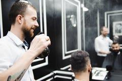 Giovane barbiere bello che fa taglio di capelli dell'uomo attraente in parrucchiere immagine stock libera da diritti
