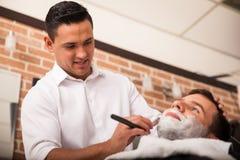 Giovane barbiere che gode del suo lavoro fotografia stock libera da diritti