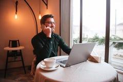 Giovane barbuto attraente che usando computer portatile e sguardo da parte Fotografia Stock