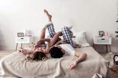 Giovane barbuto bello in una camicia bianca e nella sua moglie nel divertiresi spesso bianco dei calzini immagine stock