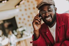 Giovane barbuto che parla sul telefono e che sorride allegramente fotografia stock libera da diritti