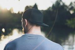 Giovane barbuto della foto che indossa cappuccio in bianco nero Fondo verde del lago park della città al tramonto Tempo di rilass Fotografie Stock