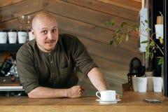Giovane barista amichevole con i baffi e barba che si siede al contatore della barra Immagine Stock