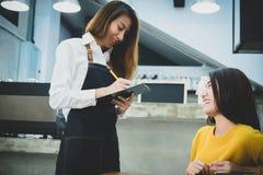 Giovane barista asiatico che prende ordine della donna nel caffè Resto del caffè Fotografia Stock