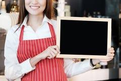 Giovane barista asiatico delle donne che tiene il menu in bianco della lavagna con lo SMI Immagine Stock
