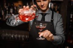 Giovane barista che fa una trasfusione un cocktail alcolico fresco nel vetro di cocktail fotografia stock libera da diritti