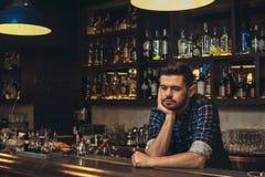 Giovane barista che si appoggia il contatore della barra premuroso fotografia stock libera da diritti