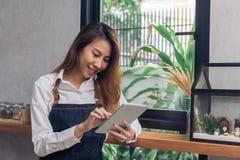 Giovane barista femminile asiatico facendo uso della compressa elettronica nella sua propria caffetteria mentre takeing irrompa i Fotografie Stock