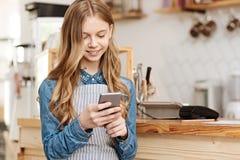 Giovane barista femminile piacevole che manda un sms sul lavoro Fotografie Stock