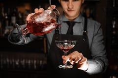 Giovane barista maschio che versa un cocktail alcolico fresco nel vetro di cocktail immagini stock libere da diritti