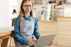 Giovane barista piacevole che posa con un computer portatile sul suo rivestimento Fotografie Stock Libere da Diritti