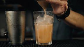 Giovane barista professionista che prepara fine dell'esterno dei cocktail sulla limonata di versamento dell'agitatore del movimen stock footage